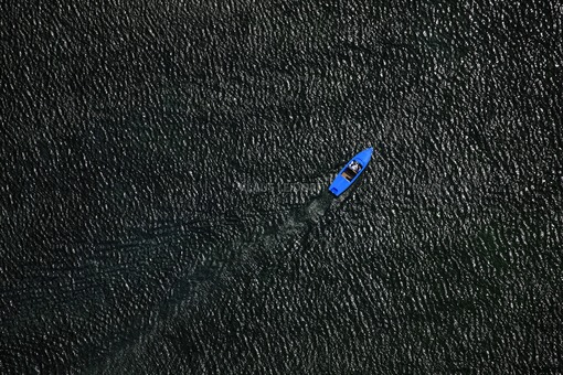Aerial view of a blue pedal boat on Lake Starnberg - Klaus Leidorf Aerial Photography