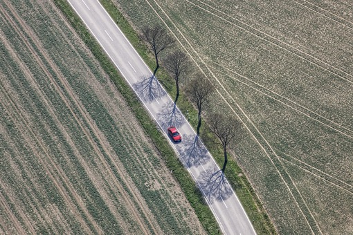 Aerial view of a red car on the country road - Klaus Leidorf Aerial Photography