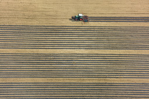 Aerial view of a tractor laying foil for a cucumber field - Klaus Leidorf Aerial Photography