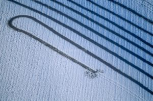 Aerial view of the traces left by a farmer on the snow-covered field with his manure spreader - Klaus Leidorf Aerial Photography