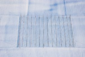Aerial view of the poles of a hop field on a snowy field - Klaus Leidorf Aerial Photography
