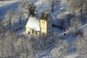 Aerial view of the small church of Heilig Kreuz at the interchange near Munich-Fröttmaning - Klaus Leidorf Aerial Photography