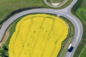 Aerial view of a rapeseed field in the curve of the country road L1093 at Blankenberg in Thuringia - Klaus Leidorf Aerial Photography