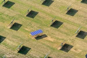 Aerial view of a solar field with moving modules near Salching. Two assembly workers are in the shade - Klaus Leidorf Aerial Photography