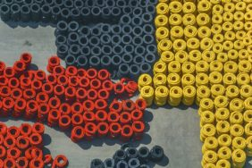 Aerial view of black, red and yellow (golden) drainage hoses in a storage bin - Klaus Leidorf Aerial Photography