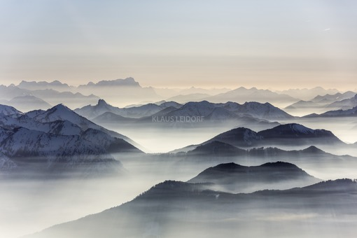 Aerial view of atmospheric haze in the valleys of the Mangfall Mountains in the Alps with a view of the Zugspitze in the background - Klaus Leidorf Aerial Photography