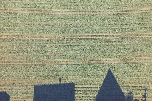 Aerial view of the outskirts of Tiefenbach-Ast. Two houses cast shadows on the field - Klaus Leidorf Aerial Photography
