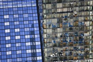 Aerial view of the SZ high-rise building in Munich, whose facade reflects the blue sky and the construction site - Klaus Leidorf Aerial Photography