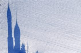 Aerial view of the shadow of the church in Haindling on a snowy field - Klaus Leidorf Aerial Photography