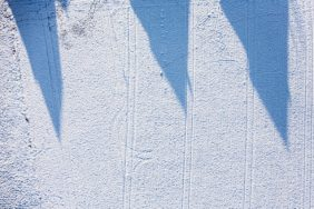 Aerial view of the shadow of three detached houses on a snowy field - Klaus Leidorf Aerial Photography