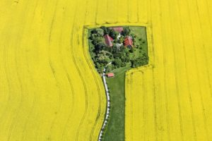 Aerial view of the former Hubstetten farm surrounded by a yellow rape field - Klaus Leidorf Aerial Photography