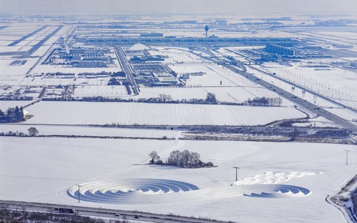 Aerial view of the snow-covered earth sign at Munich Airport; An island for the time - Klaus Leidorf Aerial Photography