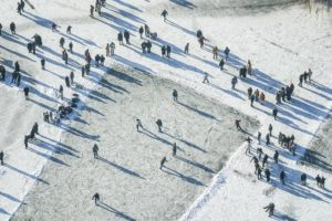 Aerial view of recreational athletes playing ice hockey on the frozen Kleinhesseloher See in the English Garden in Munich - Klaus Leidorf Aerial Photography