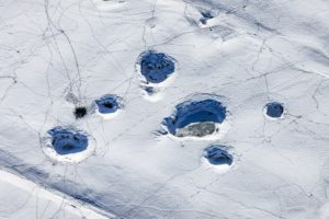 Aerial view of holes on the ground in the empty upper basin of Lake Happurg in winter with many traces - Klaus Leidorf Aerial Photography