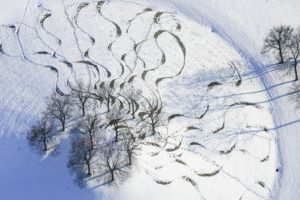Aerial view of snowboard tracks on a hill with trees in winter at the end of the A96 at Garmischer Straße in Munich - Klaus Leidorf Aerial Photography