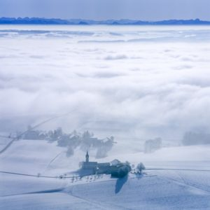 Aerial view of the winter atmosphere of the branch church St.Nikolaus in Staffing with fog and alpine panorama - Klaus Leidorf Aerial Photography