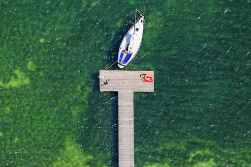Aerial view of a landing stage with sailboat at the lake promenade in Starnberg - Klaus Leidorf Aerial Photography