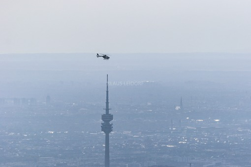 Aerial view of a Eurocopter above the Olympic Tower in hazy Munich - Klaus Leidorf Aerial Photography