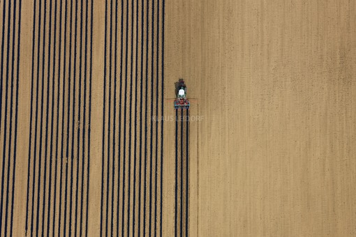 Aerial photograph of a tractor laying out straight foils for a cucumber field - Klaus Leidorf Aerial Photography