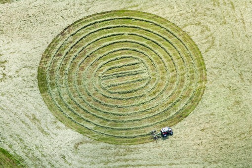 Aerial view of a tractor cutting the grass in a circle - Klaus Leidorf Aerial Photography