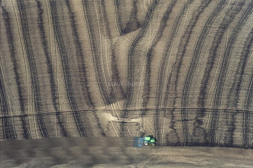 Aerial view of a green tractor harrowing a field on which slurry was previously applied - Klaus Leidorf Aerial Photography
