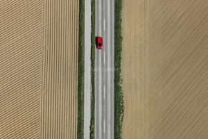 Aerial view of a red car on the country road between freshly cultivated fields - Klaus Leidorf Aerial Photography