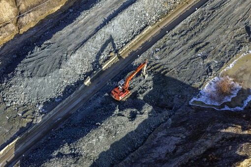 Aerial view of a red excavator in bentonite mining near Binsham - Klaus Leidorf Aerial Photography