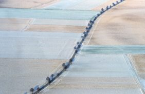 Aerial view of an avenue in lightly snowed-in farmland - Klaus Leidorf Aerial Photography