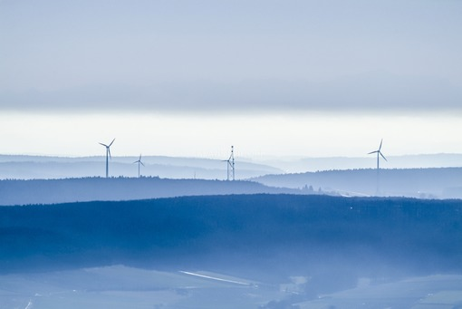 Aerial view of a hazy landscape with windmills and radio mast - Klaus Leidorf Aerial Photography