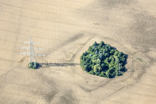 Aerial view of a green island with electricity connection in farmland - Klaus Leidorf Aerial Photography