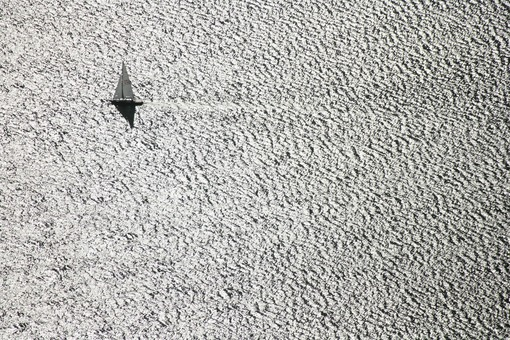 Aerial photo of a sailing boat on the Ammersee in backlight - Klaus Leidorf Aerial Photography