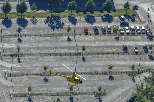 Aerial view from helicopter R44 D-HUSH over a parking lot with red car - Klaus Leidorf Aerial Photography