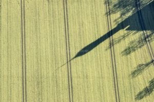Aerial view of the shadow of a church tower in the field - Klaus Leidorf Aerial Photography
