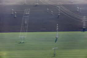Aerial view of high voltage pylons and lines on green and brown field - Klaus Leidorf Aerial Photography