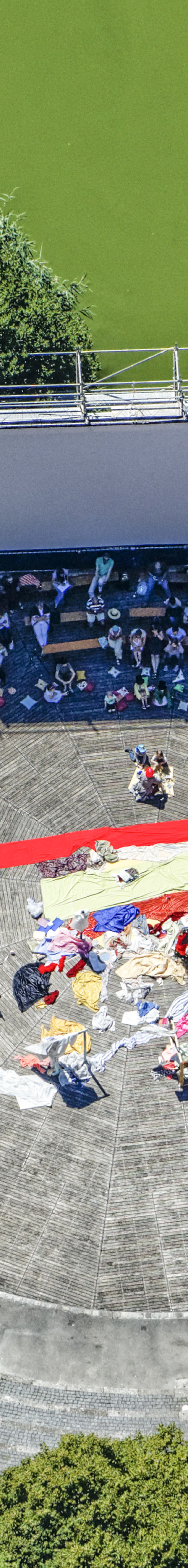 Aerial view of people in the shadow of the screen of the open-air cinema on the lake stage in Westpark Munich - Klaus Leidorf Aerial Photography