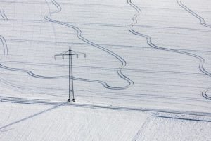 Aerial photograph of tracks on the snow-covered field under a high voltage power line - Klaus Leidorf Aerial Photography