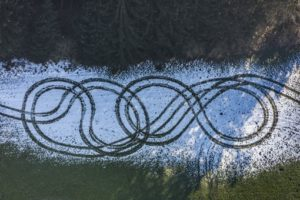Aerial photograph of tracks of a vehicle in the snow at the edge of a forest - Klaus Leidorf Aerial Photography