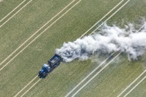Aerial view of the fertilisation work with lime on a grain field, blue tractor - Klaus Leidorf Aerial Photography