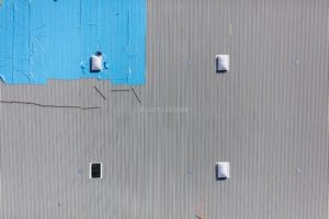Aerial view of the construction site of the new 170,000 square meter logistics center near Wallersdorf. A construction worker assembles a dormer - Klaus Leidorf Aerial Photography