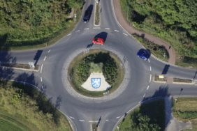 Aerial view of a roundabout with crest and red car - Klaus Leidorf Aerial Photography