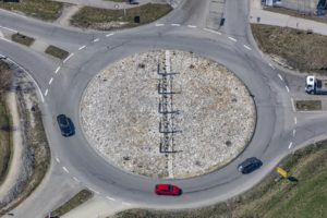 Aerial view of a roundabout with red car on the Roman Limes in Denkendorf - Klaus Leidorf Aerial Photography