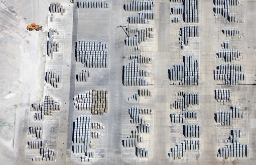 Aerial view of a storage area for concrete paving stones, a wheel loader is waiting for work - Klaus Leidorf Aerial Photography
