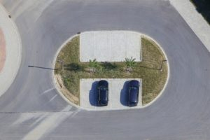 Aerial view of a parking lot in the middle of a roundabout of a residential street - Klaus Leidorf Aerial Photography