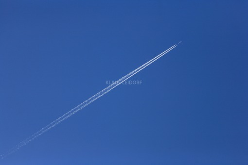 Aerial view of a passenger jet in the blue sky with contrails - Klaus Leidorf Aerial Photography