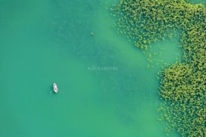 Aerial view of a rowing boat on the Pilsensee next to water lilies - Klaus Leidorf Aerial Photography