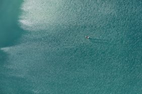 Aerial photo of a rowing boat against the light at the aquapark near Moosburg - Klaus Leidorf Aerial Photography