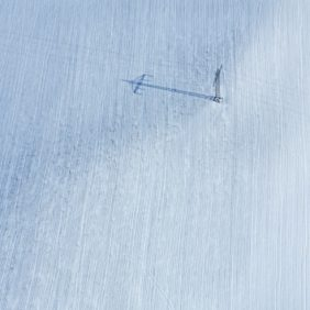 Aerial view of a power pole on a snowy field - Klaus Leidorf Aerial Photography