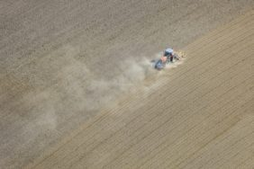 Aerial view of a tractor during sowing on the dry and dusty field - Klaus Leidorf Aerial Photography