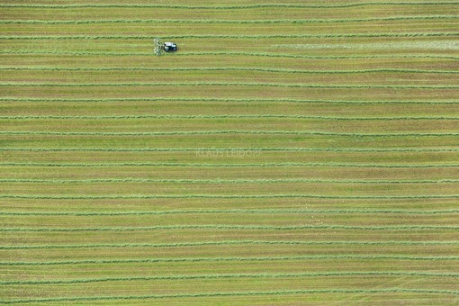 Aerial photograph of a tractor mowing meadows on grassland - Klaus Leidorf Aerial Photography