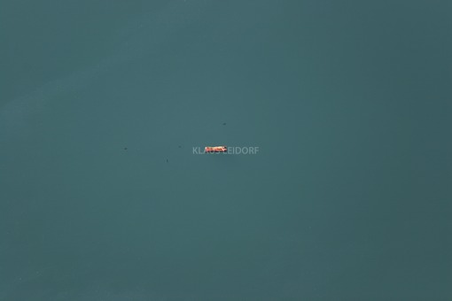 Aerial view of a vacationer on a red air mattress between ducks on the water - Klaus Leidorf Aerial Photography